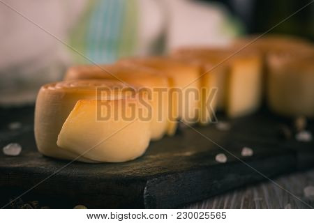 Detail Of Several Rolls From Smoked Cheese On Dark Wooden Board