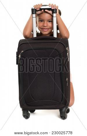 Cute african american girl hiding behind a travel suitcase - Isolated on white