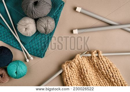 Grey And Turquoise Balls Wool And Knitting On Needles On Beige Background. Knitting As A Kind Of Nee