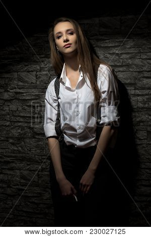 A Young Girl In A Shirt With Suspenders, Impudent And Independent. The Girl Is Holding A Cigarette.