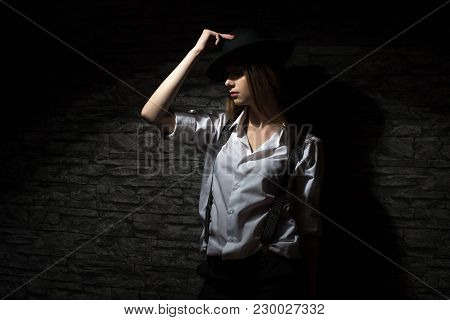 A Young Girl In A Shirt With Suspenders, Impudent And Independent. On His Head Is A Black Hat.