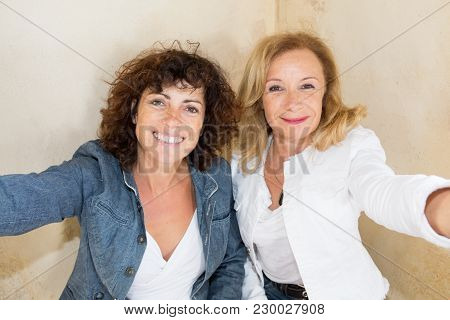Portrait Of A Happy Two Smiling Mature Couple Women Making Selfie Photo On Smartphone