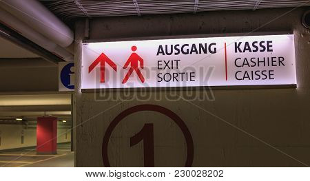 Bright Road Sign Where It Is Written Exit And Cashier In German, English And French