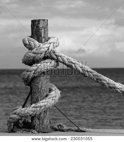 Black And White Rope On Seafront, Sea And Cloudy Sky In Evening