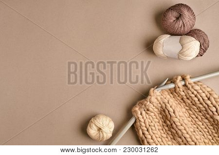 White And Brown Ball Wool And Knitting On Needles On Beige Background. Knitting As A Kind Of Needlew