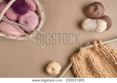 Balls Of Merino Wool Yarn, Knitting On Knitting Needles On A Beige Surface. Pink, Brown And Purple B