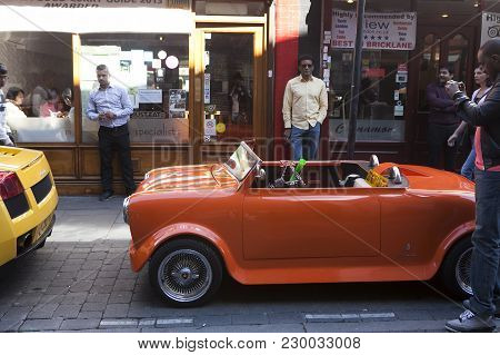 London, England - July 12, 2016 A Small Red Car Stands On The Street Brick Lane. People Walk On Bric
