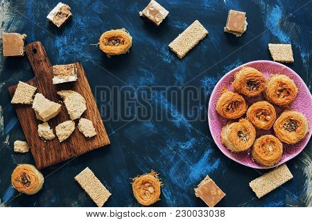 A Variety Of Oriental Sweets On A Blue Background. Baklava, Halva, Sherbet, Sesame. Top View, Copy S