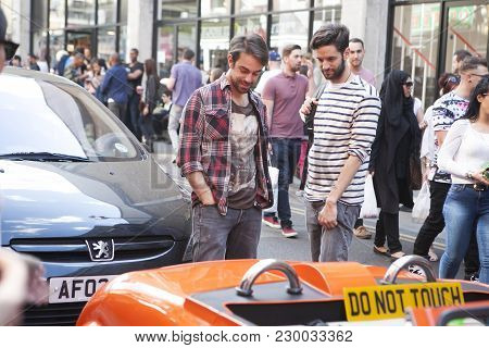 A Small Red Car With Sign Don't Touch Stands On The Street Brick Lane. People Walk On Bricklane Take