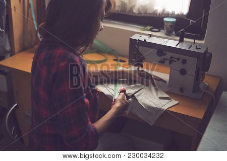 Seamstress Cutting Fabric With Scissors, Making Some Repairs. Focus On The Scissors