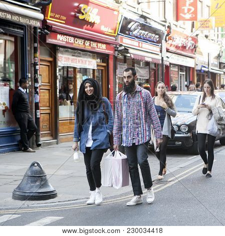 London, England - July 12, 2016 A Beautiful, Smiling Girl In Hijab With A Young Man Walking Along Th