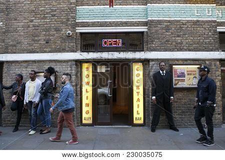 London, England - July 12, 2016 People Walk Past The Cocktail Bar At Brick Lane. A Security Guard St