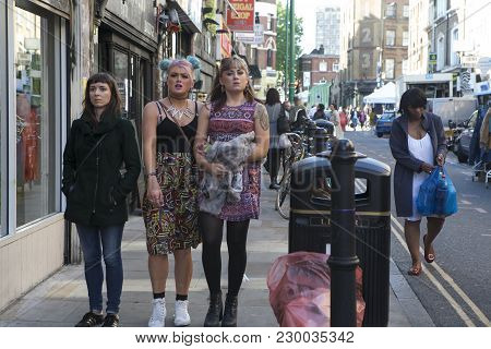 London, England - July 12, 2016 The Brunette Girl And The Blonde Are Walking Along The Brick Lane