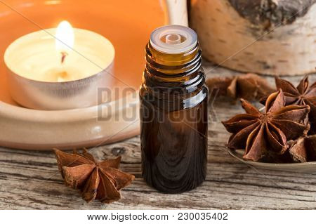 A Bottle Of Star Anise Essential Oil With Star Anise And An Aroma Lamp, Rustic Background