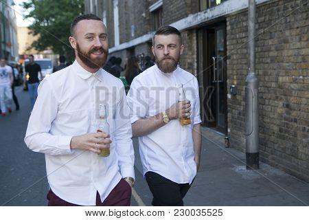 London, Uk - April 22, 2016: Two Men In White Shirts Go By Brik Lane