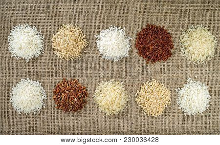 Ten Heaps Of Rice Of Different Varieties On The Background Of Sacking.