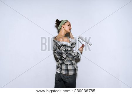 Young Girl Painter In A Plaid Shirt Colors The Wall With A Platen In White, Repair In A New Apartmen