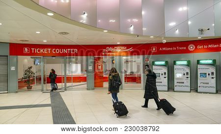 Milan Malpensa Airport - Mar 2nd, 2018: Passengers With Hand Luggage Walk Pass The Ticket Counter Fo