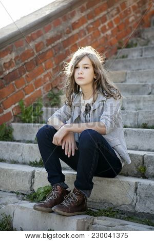 A Sad Girl With Long Hair In Jeans Of Thirteen Sits On The Steps