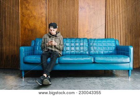 Young Man Sitting On A Blue Couch And Using A Smartphone. The Student Is Sitting On The Couch And Wr