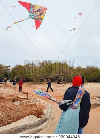 Athens, Greece - February 18, 2018: Man Selling Kites And Others Flying Them As Is The Tradition On