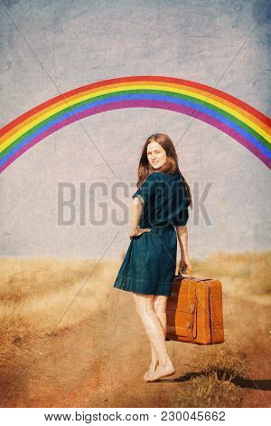 Brunet Girl With Suitcase Walking On The Road At Countryside In Summertime With Rainbow On Backgroun