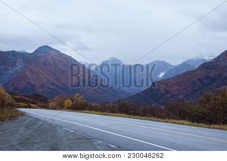 A Road In The Alaskan Mountains In Autumn. Clouds Overhead, Bluish Morning Light, Snow On The Tops O