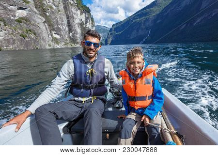 Happy Boy With His Father Driving The Motorboat, Geirangerfjord, Norway. They Are Enjoying The Momen