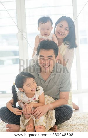 Chinese parents and children piggy back. Happy Asian family spending quality time at home, natural living lifestyle indoors.
