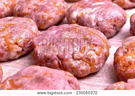 Fresh Cutlets Of Beef And Pork Lie On A Wooden Board Covered With A Film. Cutlets Lie In Several Row