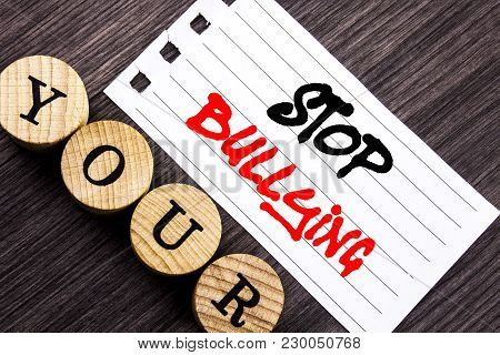 Writing text showing  Stop Bullying. Business photo showcasing Awareness Problem About Violence Abuse Bully Problem written tear note paper sticky note the wooden background. poster