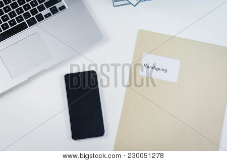 German Termination Letter Or Dismissal From Employment On A Desk Lying Alongside An Open Laptop Comp