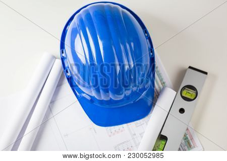 Architect Or Structural Engineers Office With A Blue Hardhat On A Desk Top With Blueprints Or Plans
