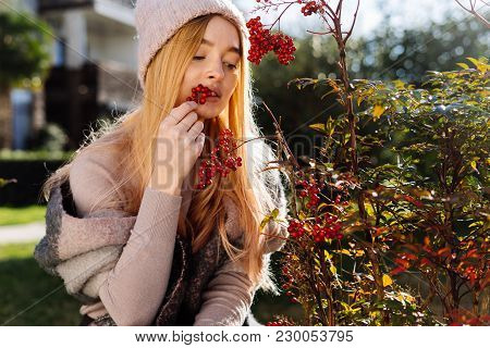 Young Beautiful Blond Girl In A Pink Hat Walking In The Garden, Trying The Berries On The Palate