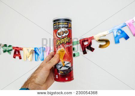 Paris, France - Jan 6, 2018: Pringles Original Chips In Male Hand Against Joyeux Anniversaire Text H