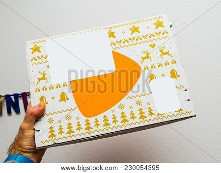 Paris, France - Jan 1, 2018: Man Holding Against White Background A Box Containing Fashion Clothes B