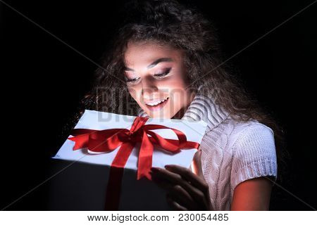Portrait of a beautiful young brunette peering in a gift box