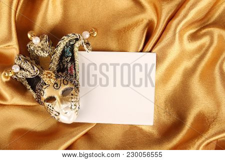 Carnival Mask Lying On A Yellow Silk And A Sheet Of White Paper