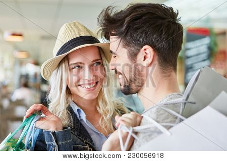 Happy young couple is flirting while shopping together in shopping mall