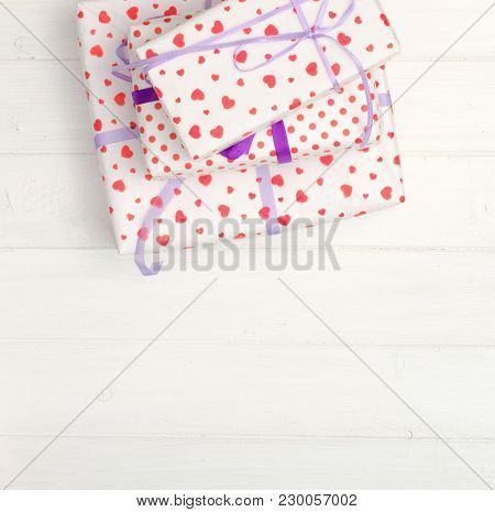 Lovely giftboxes on white wooden table wrapped in heart pattern paper with purple ribbon. op view and copyspace. space for caption, empty space for text
