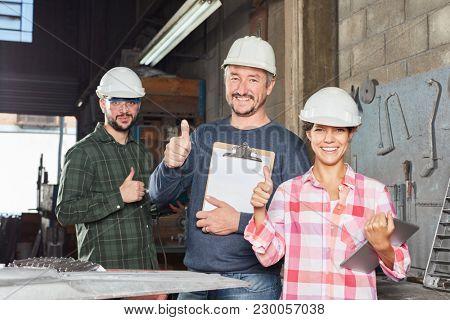 Successful team of metalworkers holding thumbs up in metallurgy workshop