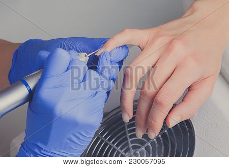 Closeup Shot Of Manicurist In Blue Rubber Gloves Cleans Cuticle On Female Nails Using A Milling Cutt