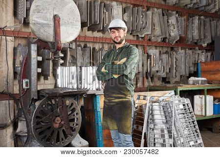 Man as worker smiles and stands proud in foundry of metallurgy factory