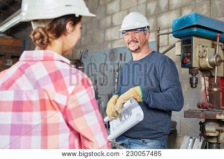 Craftsman and metalworker in metal construction workshop