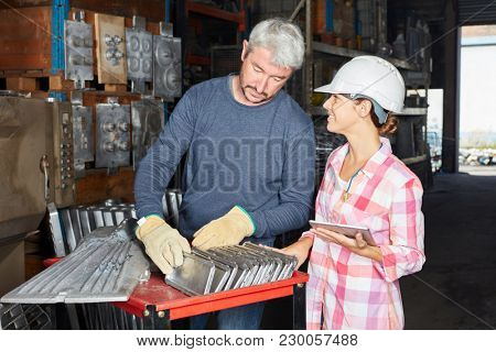 Woman as metalworker in apprentice lesson with blue collar worker as instructor
