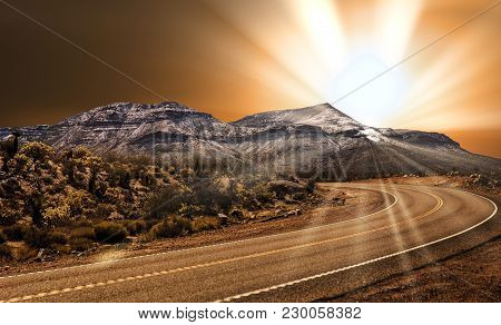 A Highway Curving Through A Desert With Snow Dusted Mountains And Green Foliage In A Spring Time Lan