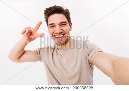 Smiling guy with brown hair showing peace sign on camera while photographing himself isolated over white background