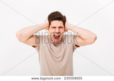 Disappointed man 30s grabbing his head or covering ears while screaming due to annoying noise isolated over white background