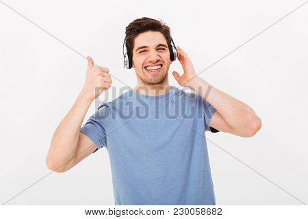 Pleased guy in casual t-shirt listening to music via headphones and gesturing thumb up with smile isolated over white background