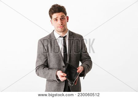 Portrait of a sad young businessman showing empty wallet isolated over white background
